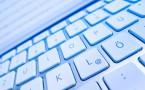 Die Tastatur eines Computers vor einem Bildschirm. Datenverarbeitung und Internet