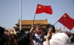 A child waves the national flag as people gather on Tian'...