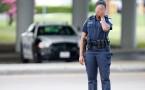 A deputy redirects traffic near a standoff between police and a single gunman in Hutchins, Texas
