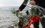Young man leaves red cloves at the Caspian seaside to mark...