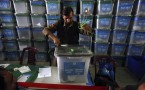 An Afghan election worker opens the lock to a ballot box